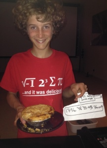 """Eating pie on Pi Day.  For the mathematically rusty, Max's T-shirt says: """"i 8 sum pi... and it was delicious."""" And the sheet of paper shows the volume of the pie he ate.  Using π."""