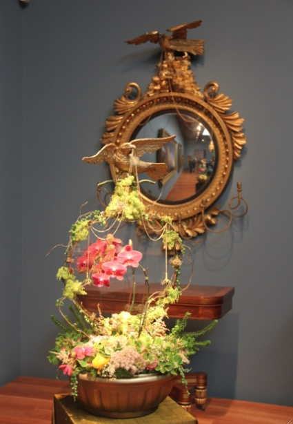 This display looked as if it was a mirror, like the that inspired it. But closer inspection showed that the flowers framed clear glass, and a matching sprig of orchids stood behind the glass as if it was a reflection.