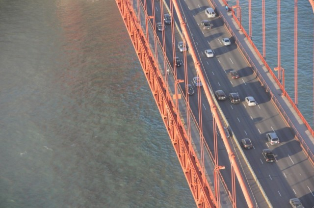 The Golden Gate Bridge, reflecting orange on the surface of the water
