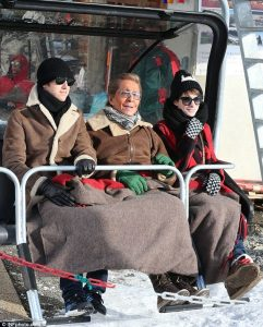 Riding a chairlift in style, with footrests and blankets. This one happens to have Anne Hathaway, her husband and a friend, in Switzerland.